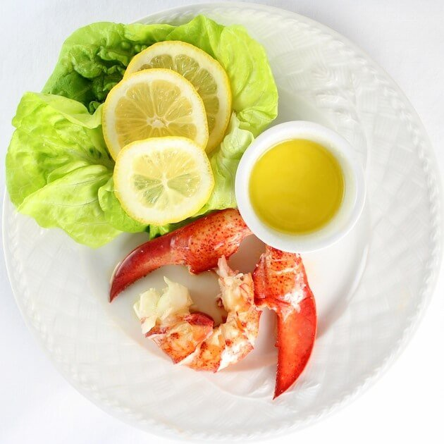 Lobster claw and tail meat on plate with drawn butter