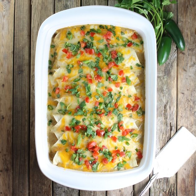 Casserole dish full of Cheesy Chicken Enchiladas with spatula and jalapenos