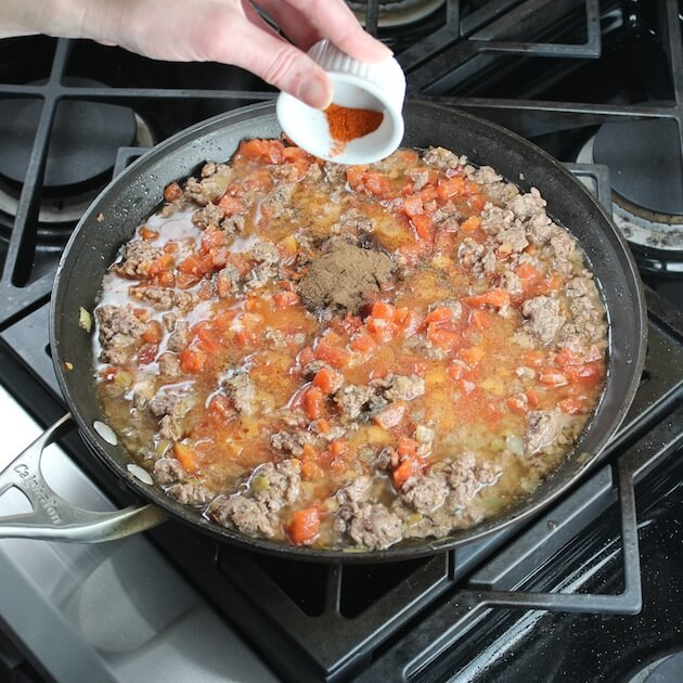 Adding cayenne to pan of ingredients sauteeing