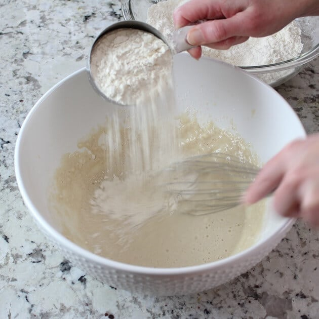 Adding flour to pizza dough batter in mixing bowl
