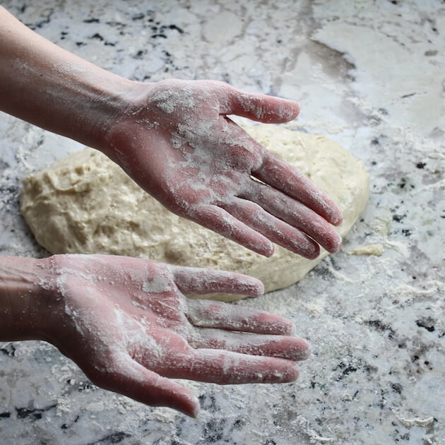 floured hands ready to roll pizza dough