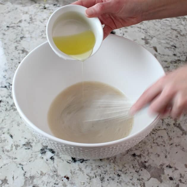 Adding oil to yeast in mixing bowl