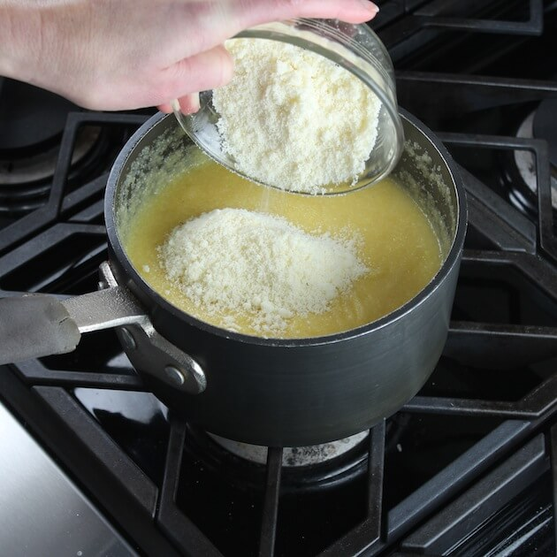 Adding parmesan cheese to polenta while cooking in saucepan