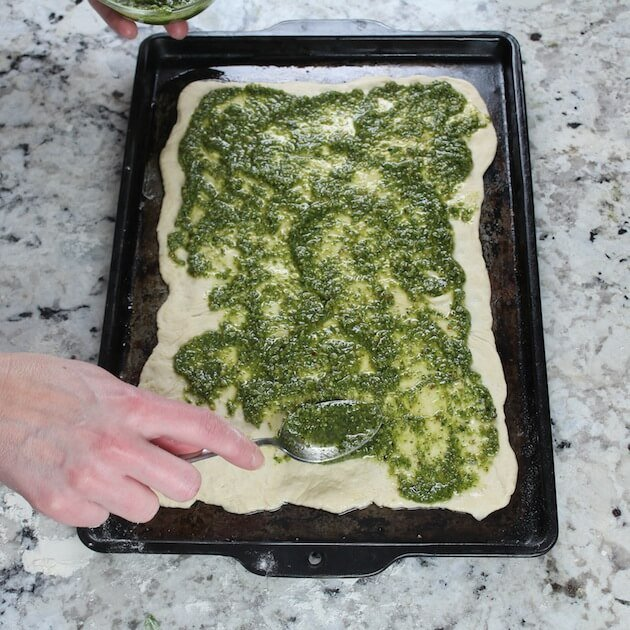 Adding pesto to pizza dough on baking sheet