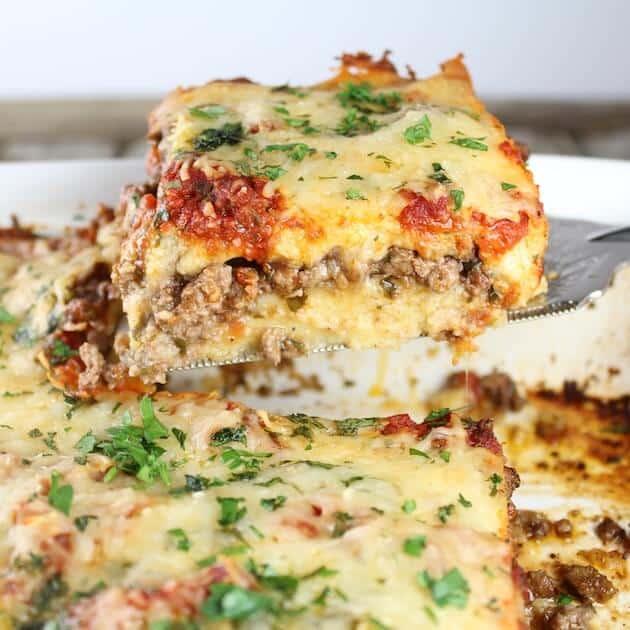 Spatula holding a piece of Lamb Lasagna With Parmesan Polenta above baking dish