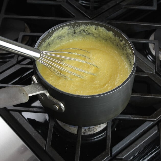 Pot of cooked instant polenta with wire whisk