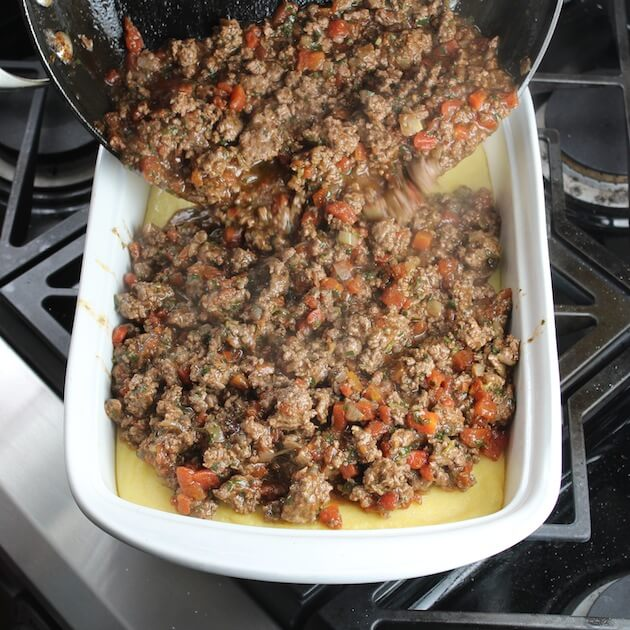 Adding lamb lasagna meat mixture to casserole dish with layer of polenta in the bottom