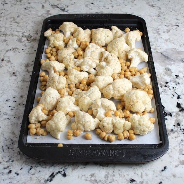 Florets of cauliflower & chickpeas on baking sheet ready for oven
