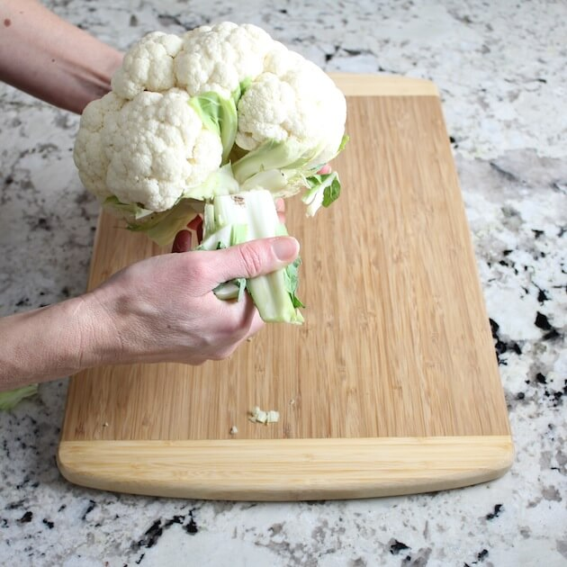 Remove leaves from head of cauliflower