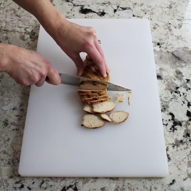 slicing chicken on cutting board