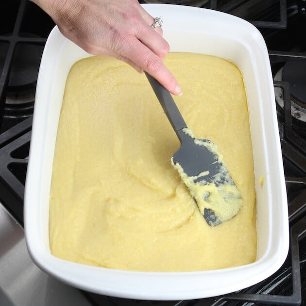 smoothing out polenta on bottom of a casserole dish