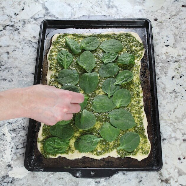 Adding spinach to Chicken Pesto Pizza