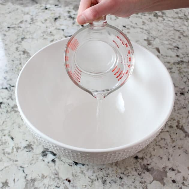 Pouring water into empty mixing bowl
