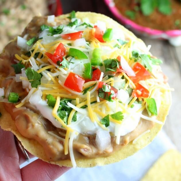 Hand holding Mexican pizza with refried beans and toppings