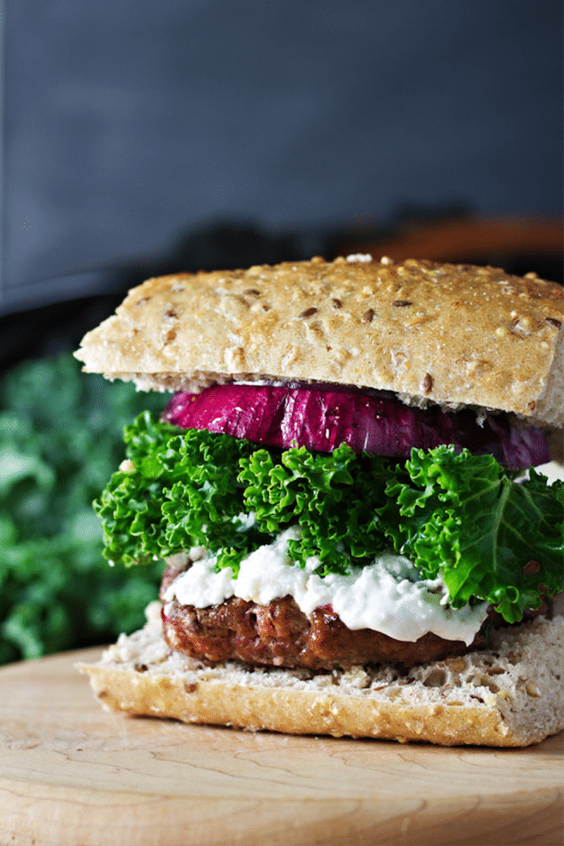 Burger on hearty bread with kale and red onion