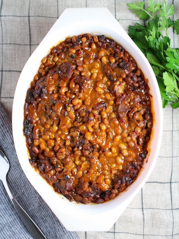 BBQ Baked Beans in a serving dish with parsley garnish
