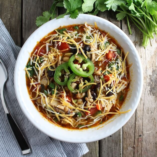 White bowl of Smoky Chicken Chili garnished with shredded cheese and jalapeno slices