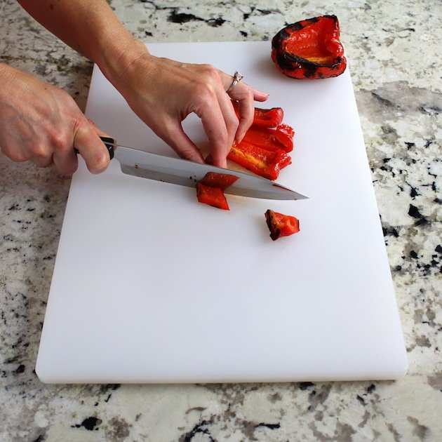 Chopping grilled red pepper on cutting board