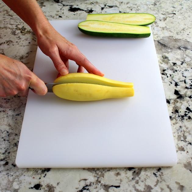 Slicing yellow squash on cutting board