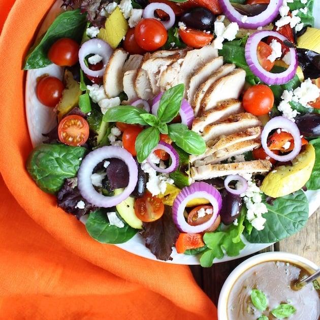 Grilled Mediterranean Chicken Salad on plate with orange napkin