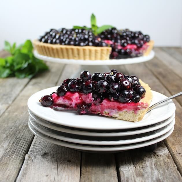 Slice of Blueberry tart on stack of serving plates