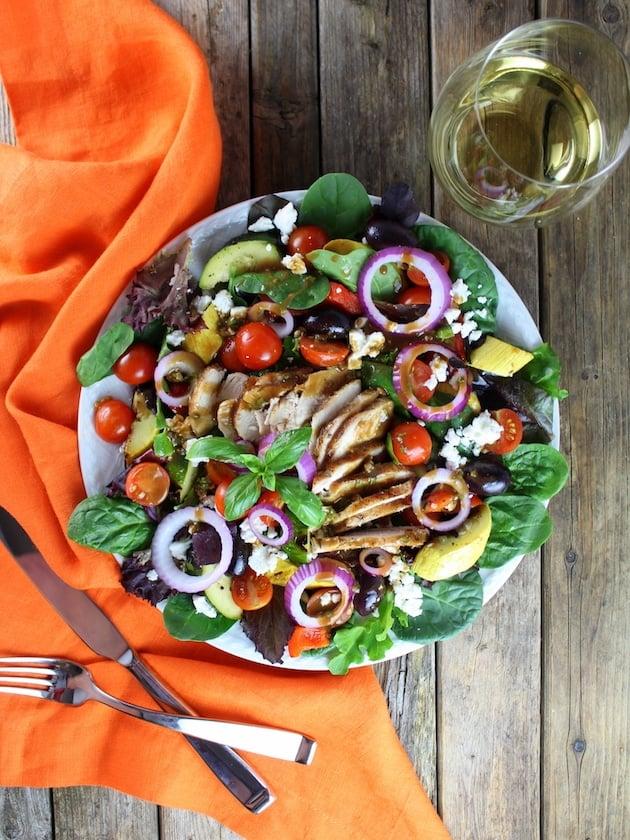 Grilled Mediterranean Chicken Salad with orange napkin and silverware