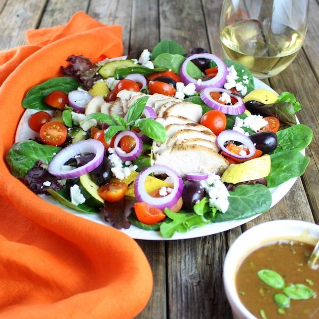 Grilled Mediterranean Chicken Salad with ramekin of dressing and glass of white wine
