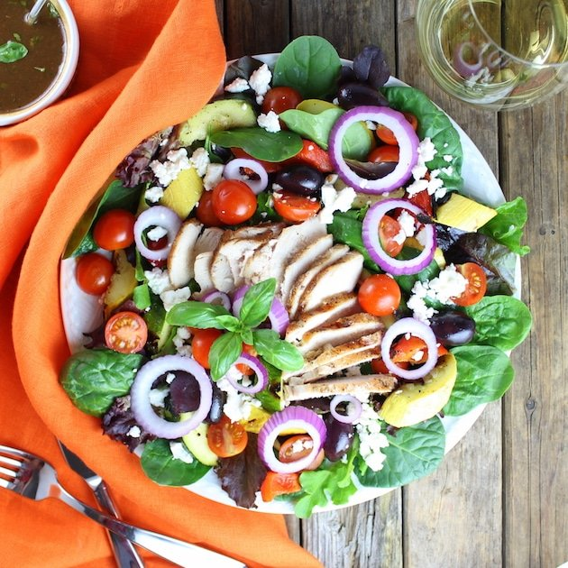 Grilled Mediterranean Chicken Salad on diner plate with silverware and glass of white wine
