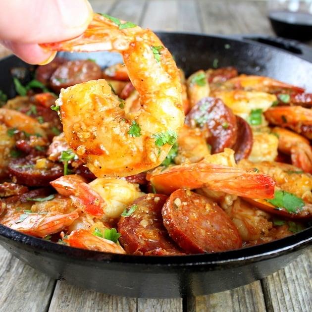 Hand holding shrimp in front of skillet of chorizo shrimp