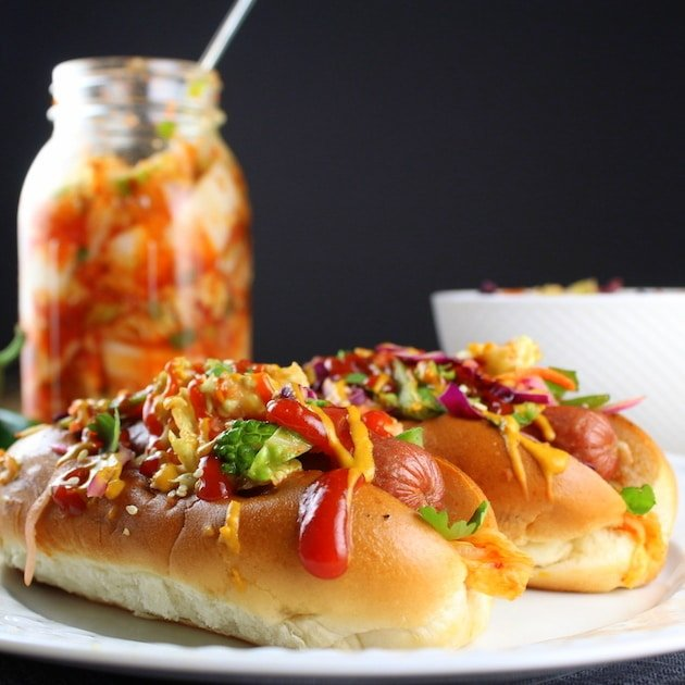 Two Korean Slaw Hot Dogs on plate with mason jar of Kimchi in background