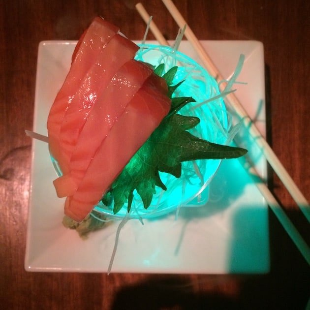 Sushi served on a neon lit glass dish with chopsticks