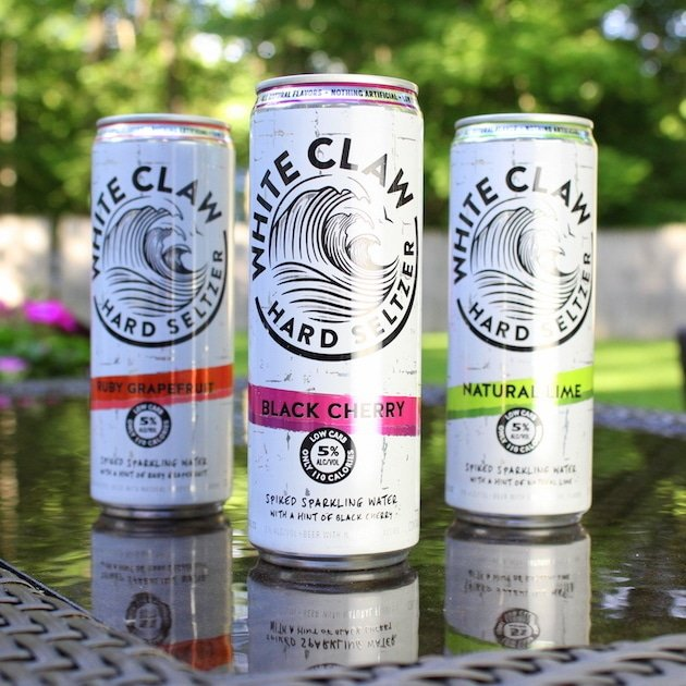 Three cans of White Claw Hard Seltzer eye level in backyard
