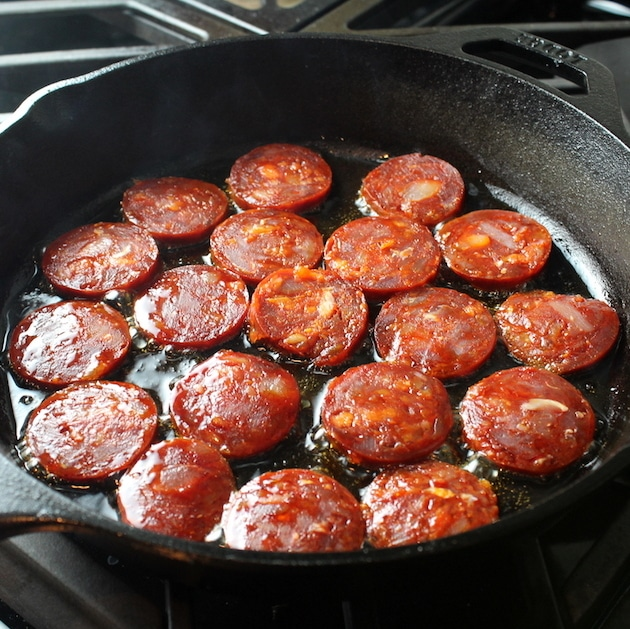 Chorizo sauteeing in cast iron skillet on stovetop