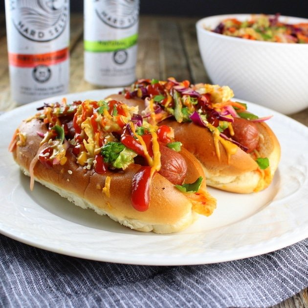Two Korean Slaw Hot Dogs on plate with bowl of Asian slaw in background