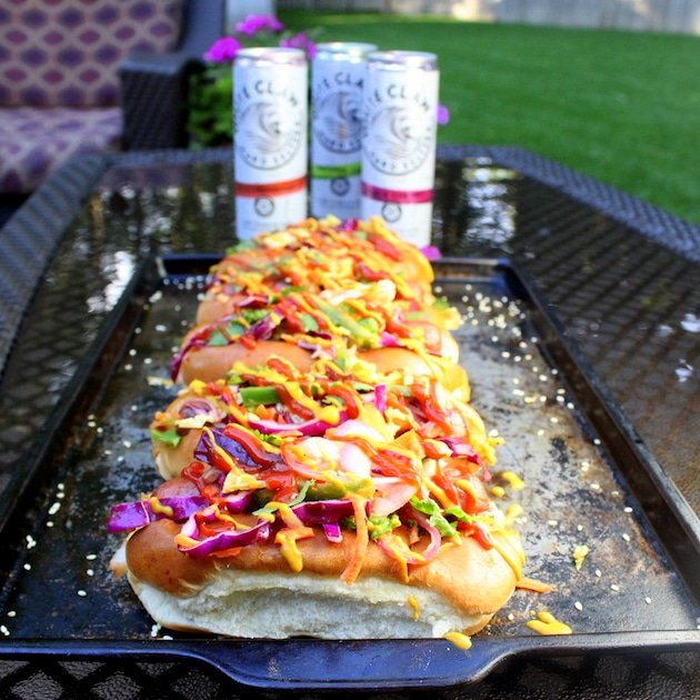 Five Korean Slaw Hot Dogs lined up on a cookie sheet on a backyard table