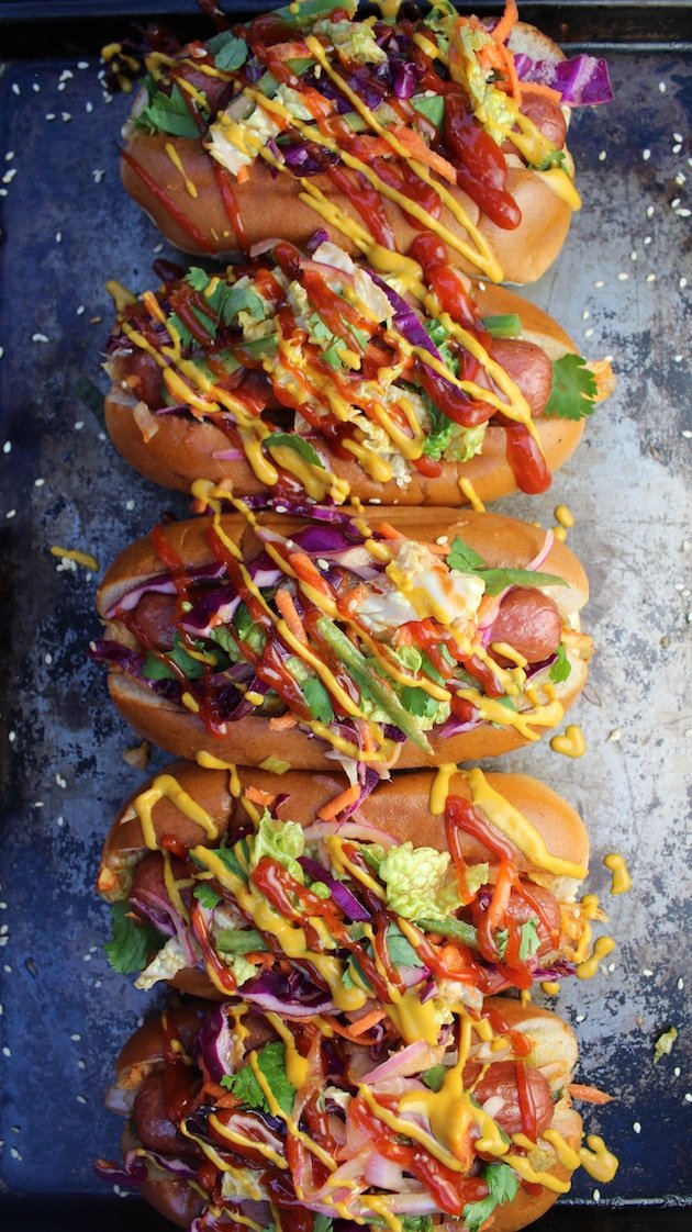 These Korean Slaw Dogs are an amazing game-day favorite! all-beef hot dogs loaded with Korean BBQ sauces, spicy kimchi, & sweet/tangy slaw, topped w/kickin' ketchup & mustard.  Asian fusion in a bun! #hotdogs #kimchi #slaw https://tasteandsee.com