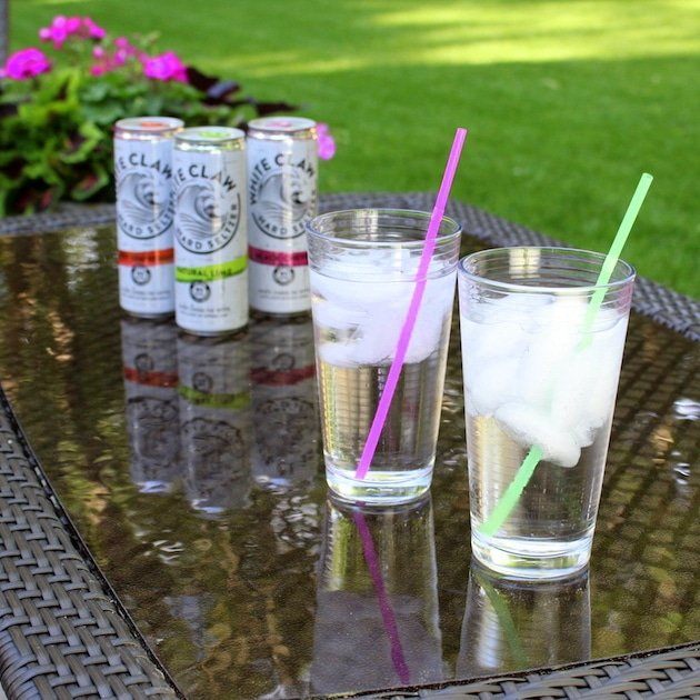 Glasses with ice and straws in backyard, with White Claw Hard Seltzer cans in background