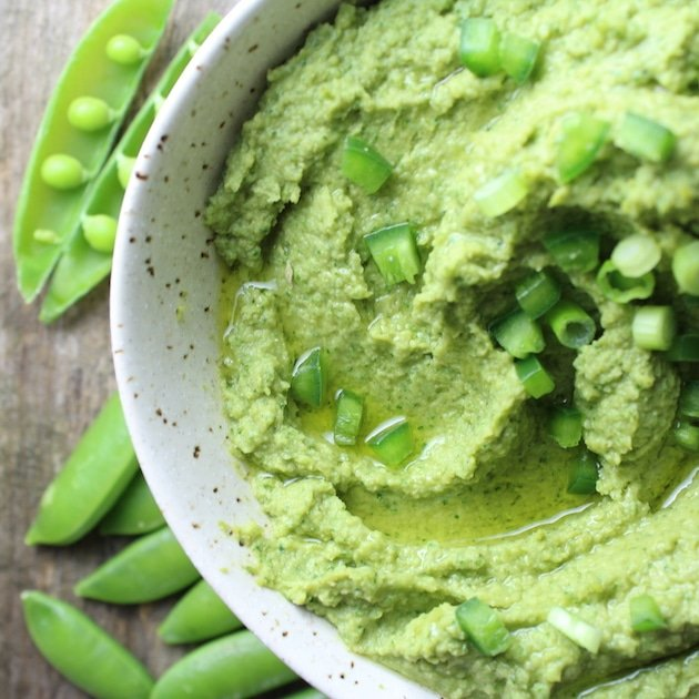 Partial bowl of Spicy Green Hummus with chopped onions and olive oil