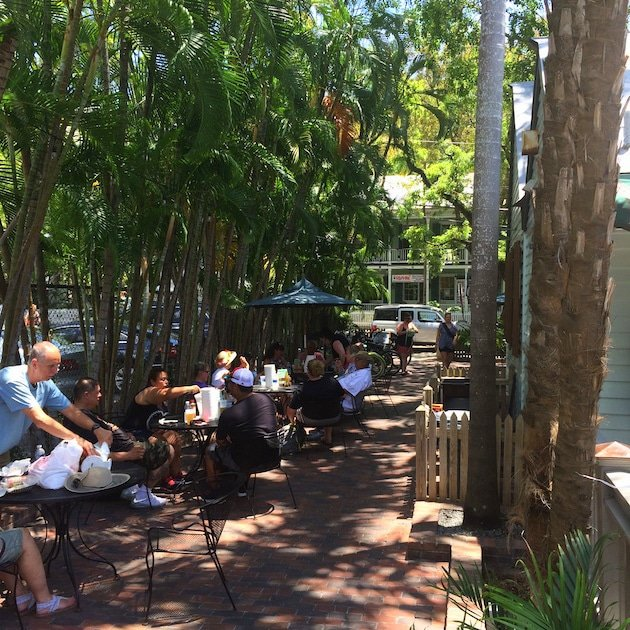People eating at outdoor tables in tropical setting at Key West Garbo\'s Grill