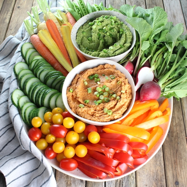 Platter loaded with fresh veggies, Sun-Dried Tomato Goat Cheese Dip and Spicy Green Hummus