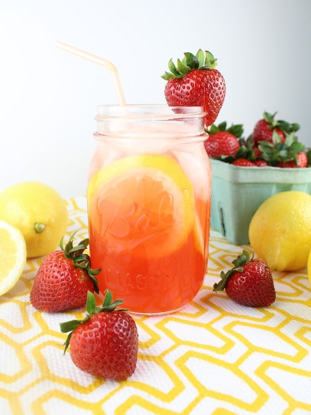 Mason jar of Strawberry Lemonade with fresh strawberries in the background
