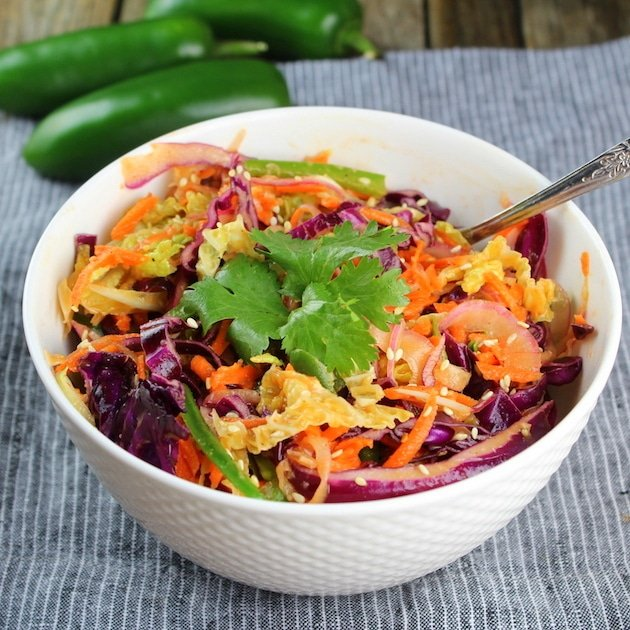 Bowl of asian slaw with jalapenos in the background