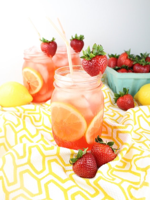 Loaded Strawberry Lemonade in mason jars on a yellow patterned tablecloth