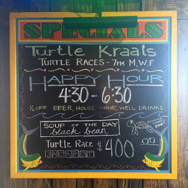 Chalkboard of bar specials and turtle race schedule at Turtle Kraals Key West