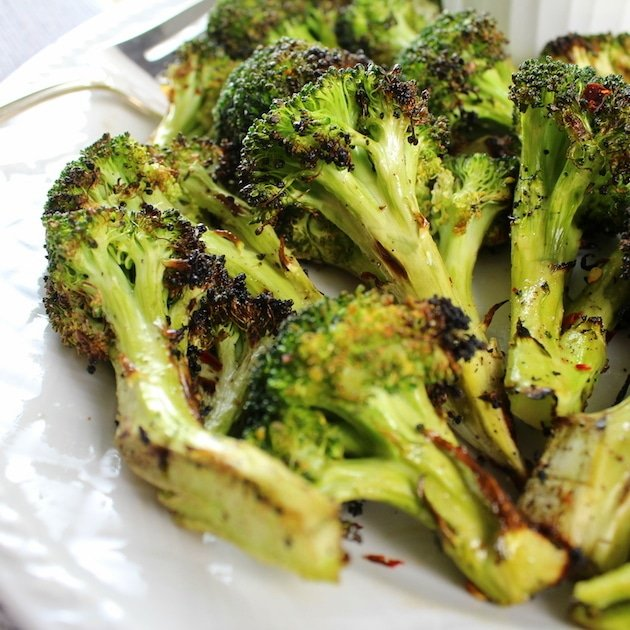Grilled Broccoli florets stacked on white plate