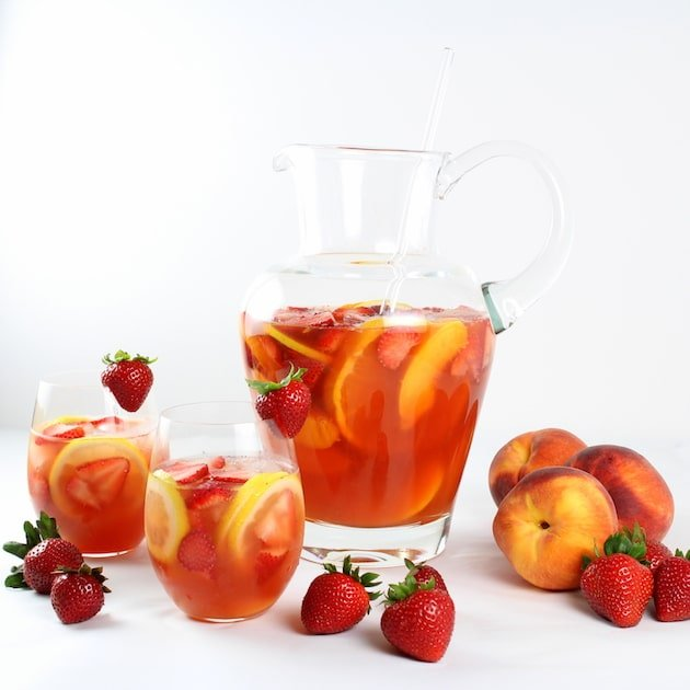 Large glass pitcher of peach sangria