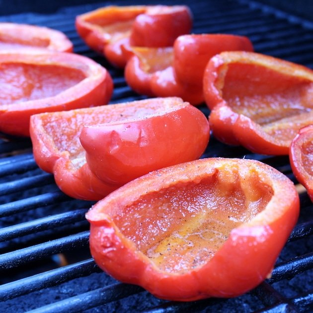 halved red bell peppers on the grill