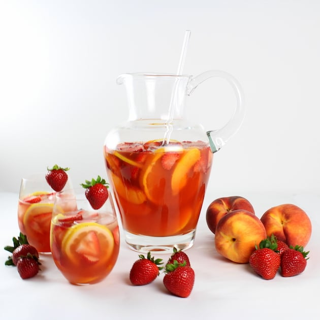 A bowl of fruit on a table, with Peach and Sangria