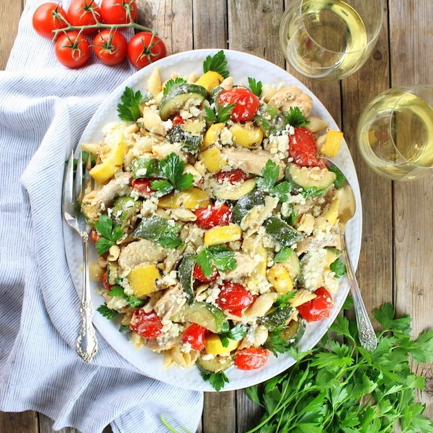 Serving dish of Grilled Chicken and Squash with Tomato Feta Pasta on farm table