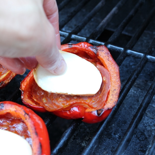 adding fresh mozzarella to red bell peppers on the grill